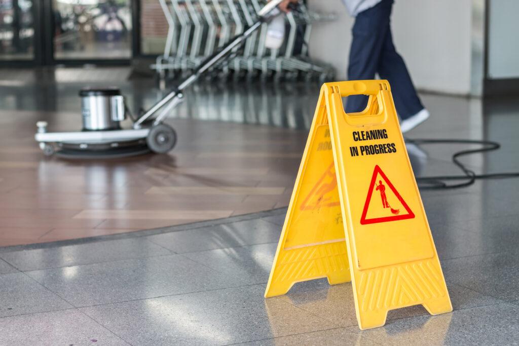 εργαζόμενος που καθαρίζει το πάτωμα με μηχανή στίλβωσης